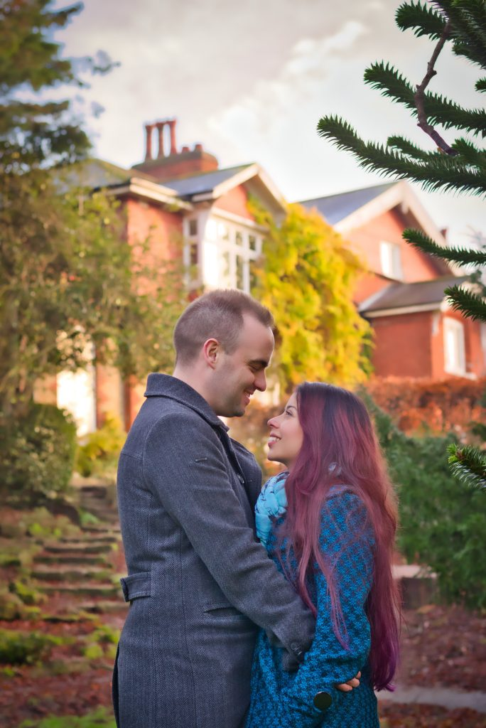 couple looking at each other standing in front of a beatiful house