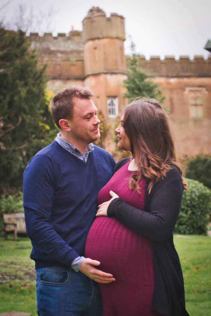 expecting parents in front of a castle