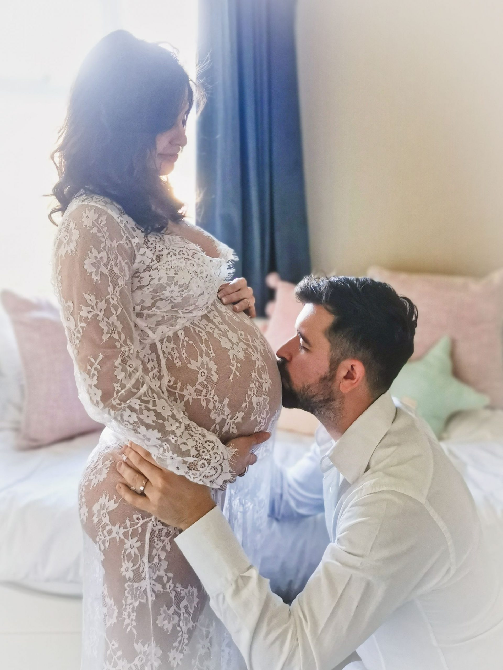 Maternity Photography dad kissing baby bump in the nursery