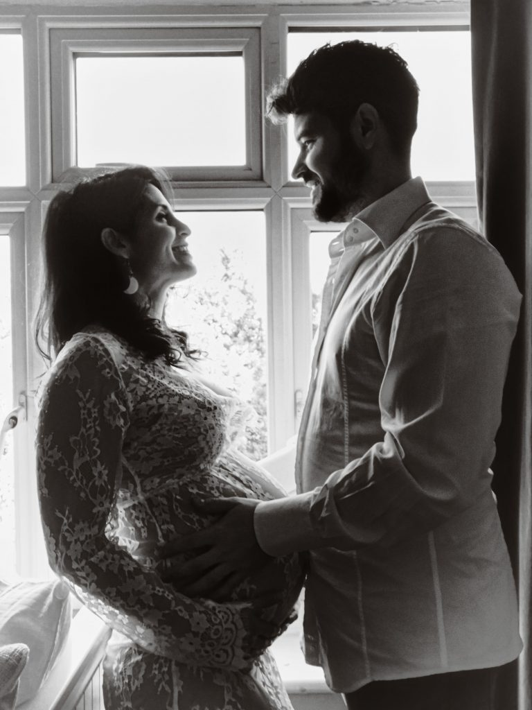 black and white portrait of expecting parents looking at each other in front of a window