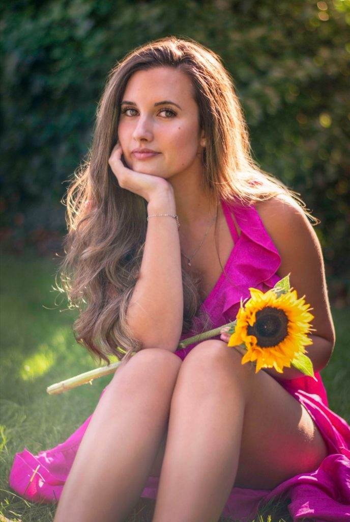 beautiful portrait of a girl dressed in pink holding a sunflower