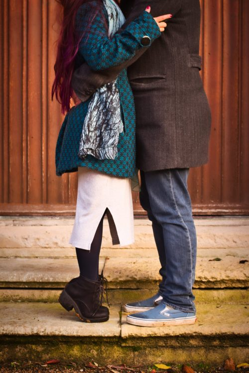view of the feet of a couple standing in front of each other she is on her tip toes to reach out and kiss him